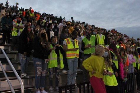 Students on senior night don neon colors instead of the normal college merchandise.